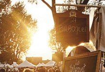 Des festivaliers et une ardoise au soleil couchant au Bières et Saveurs de Chambly