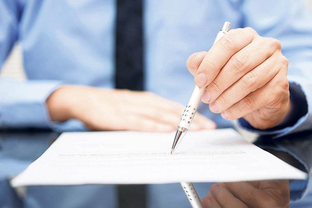 Un homme rempli un formulaire avec un stylo
