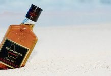 Bouteille de rhum Mount Gay semi enfouie sur une plage de sable blanc