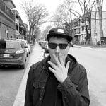 Fred Jourdain marchant sur le trottoir avec sa casquette, ses lunettes soleil et une cigarette à al bouche