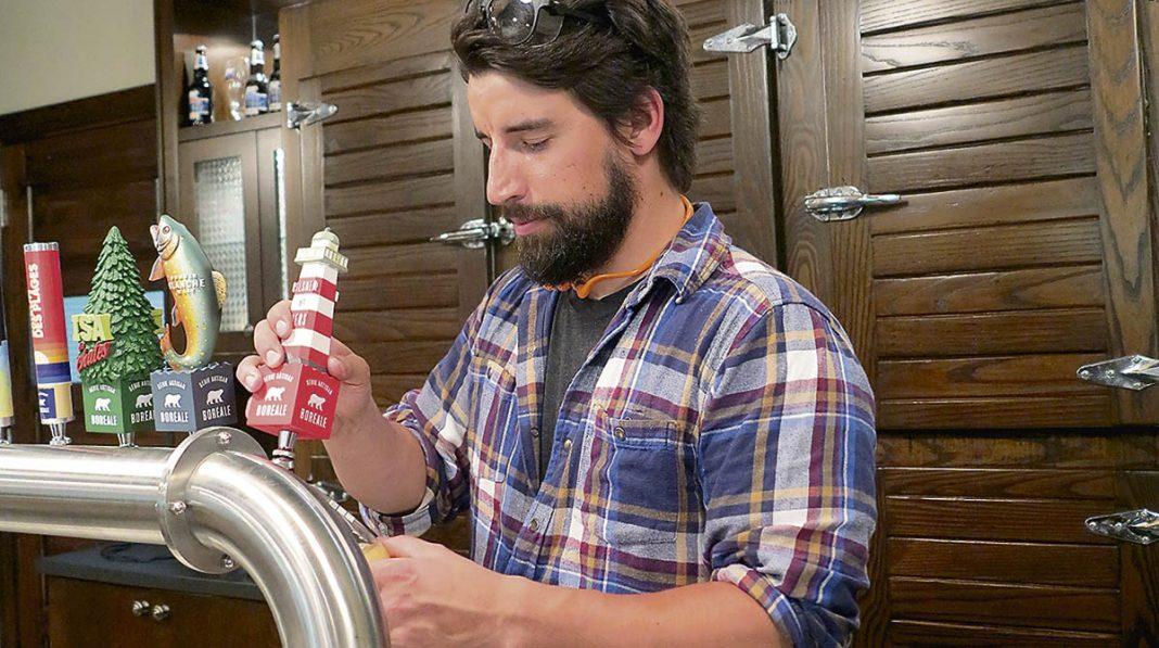 Gabriel Dulong qui coule une bière Boréale à la microbrasserie