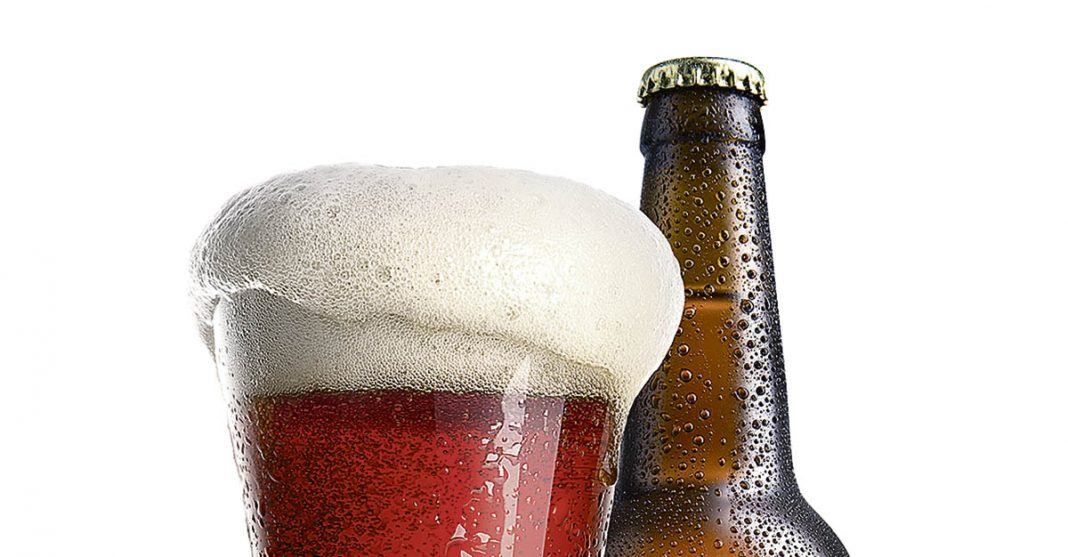 Un verre d'Irish Red Ale servie avec un superbe collet à côté de sa bouteille