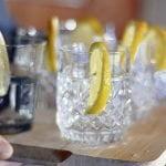 Gros plan sur une blanche de bois avec 6 verres de gin sur glace avec un twist se faisant transporter