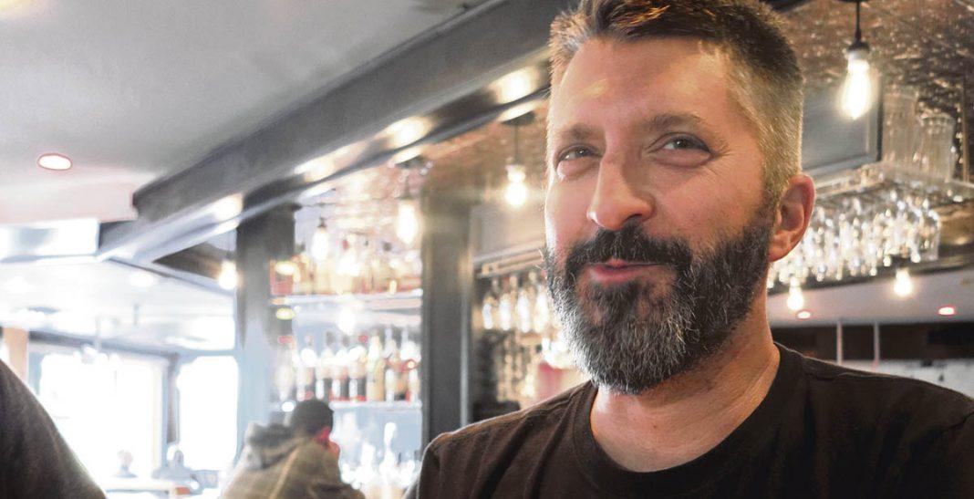 René Huard derrière le bar du petit medley, sourire en coin derrière sa barbe poivre et sel.