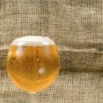 Verre de bière sur une table de bois à côté d'une bouteille