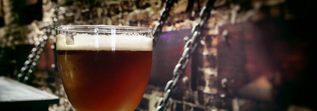 Un calice rempli de bière de Noël rousse sur une tablette posée avec des chaines sur un mur de pierres