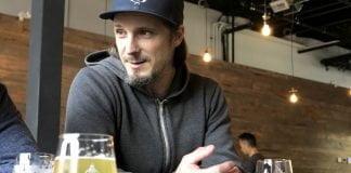 Luc «Bim» Lafontaine avec sa casquette et son hoodie attablé au bar avec une bière