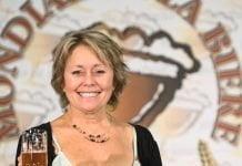 Jeannine Marois devant le logo du Mondial de la bière, un verre de bière à la main