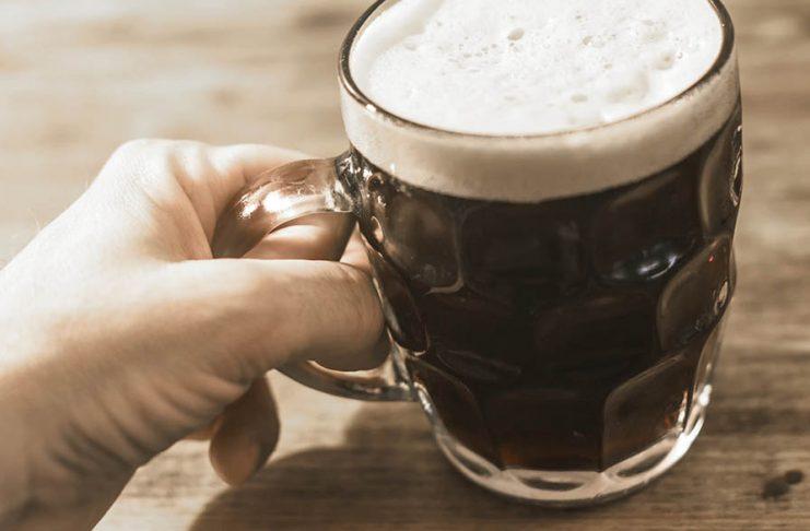 Une main tenant un bock de bière noire au collet généreux