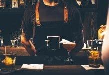 Un barman présentant un cocktail derrière son bar