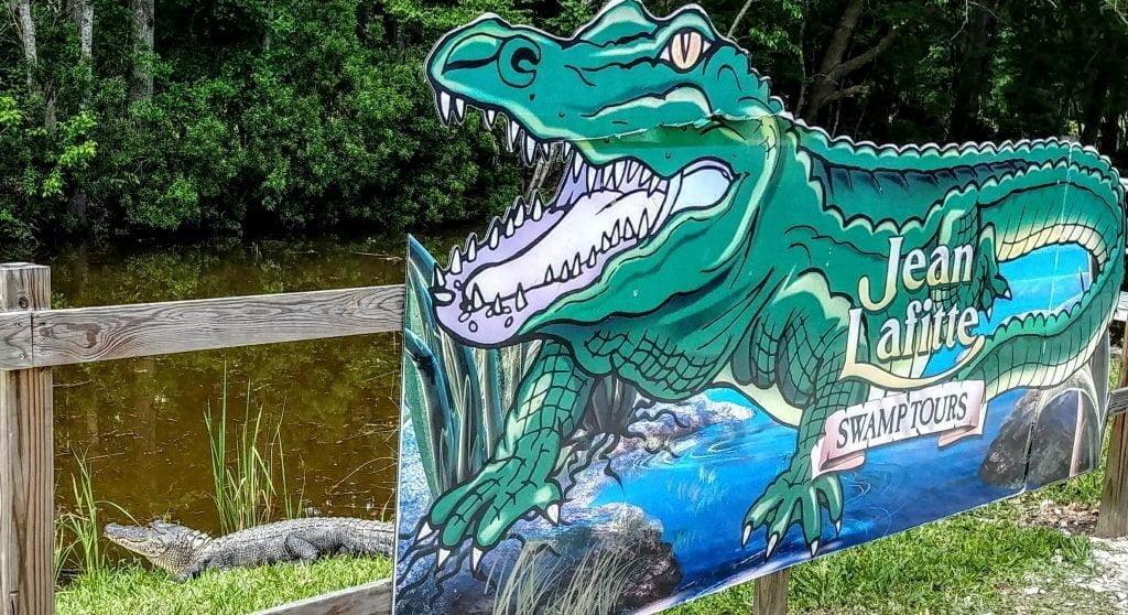 Un alligator à côté de la pancarte annonçant le Jean Lafitte Swamp Tour