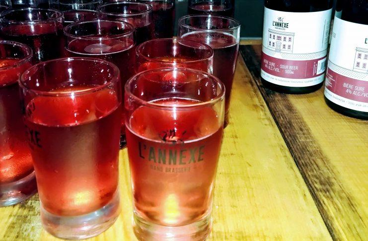 Quelques verres et deux bouteilles de la Berliner Weiis Kettle Sour au framboise de L'Annexe nanobrasserie sur une table de bois.