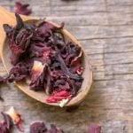 Une cuillère de bois pleine de pétales d'hibiscus séchées