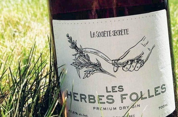 Une bouteille du gin Les Herbes Folles dans l'herbe près de la distillerie La Société Secrète de Gaspésie