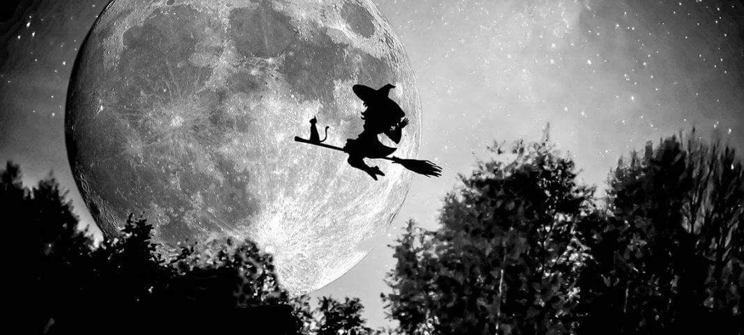La silhopuette d'une sorcière volant deavnt la plaine lune sur un balais avec son chat