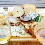 Un plateua de fromages avec quelques nois et des tranches de pommes accompagnés de différents types de cidres