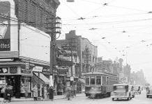 Une photo d'époque montrant une rue ontarienne avec son tramway, des voitures, des passants et ses ensignes
