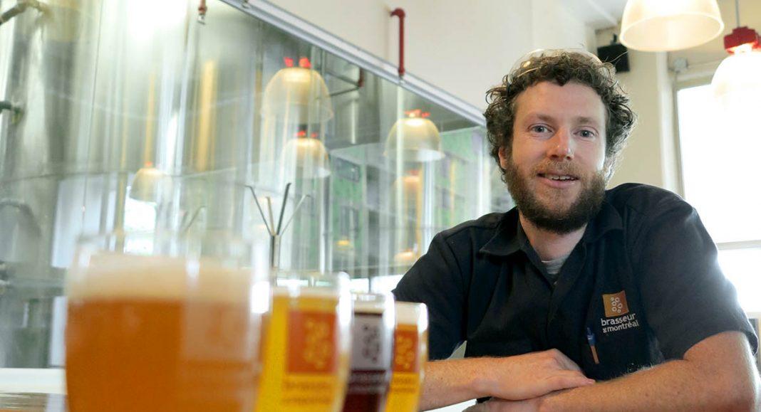 Mike Harrison accoudé au bar devant les cuves de brassages de Brasseur de Montréal avec quelques unes de ses bières